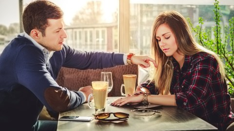An overwhelmed mom with ADHD confides in a friend over coffee at a cafe.