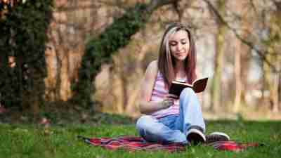 A girl with learning disabilities reads a book.