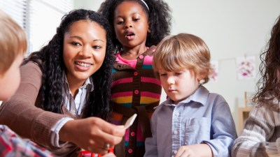 A woman works with two children with learning disabilities