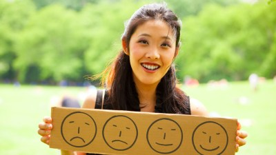 ADHD bipolar woman holds a sign with smiley faces