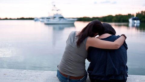 A woman with ADHD showing compassion for a friend who is depressed by the water on a dock