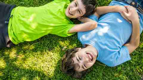 Boys laying outside in the grass over summer, not learning anything
