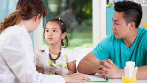 A young girl at a doctor's appointment over summer, learning how to use a stethoscope