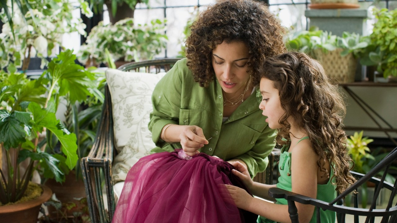 Mother teaching her daughter sewing over summer to prevent learning loss