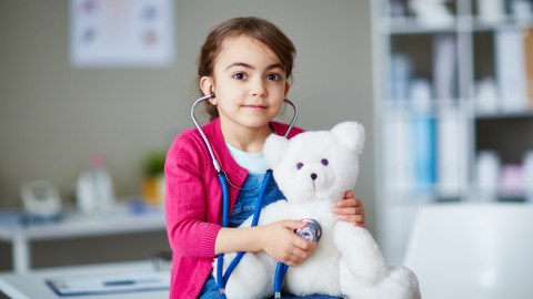 A gAn ADHD girl with SPD examines her teddy bear.irl with SPD examines her teddy bear.