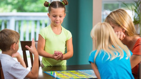 Family playing a board game to kick off the new school year