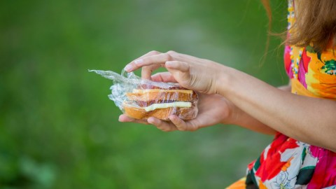 A woman with ADHD holds a sandwich in her hand while trying to lose weight
