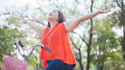 A woman with ADHD rides a bike. Regular exercise is crucial for weight loss.