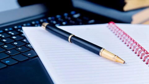 A pen and a notebook filled with strategies for limiting screen time