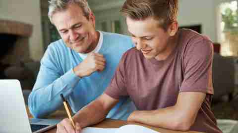 A father helping ADHD his son with his homework because quality time is one way to motivate a teenager.