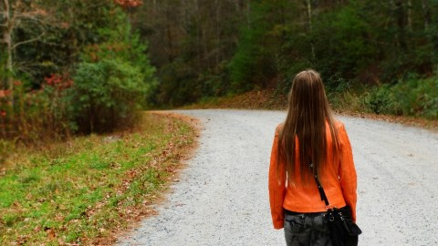 A girl walks alone on a road. Her parents wonder how to motivate a teen.