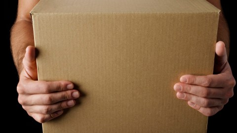 Close-up of man with ADHD holding cardboard box