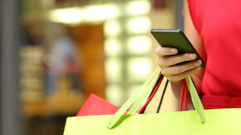 A woman carrying shopping bags shopped smart to avoid clutter.