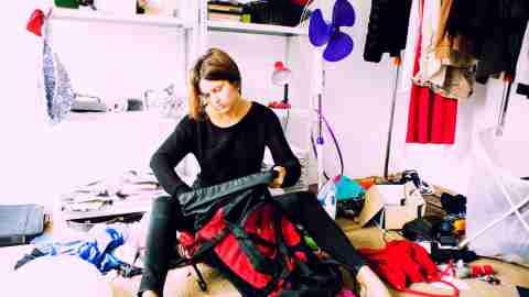 A woman sits on the floor of a room covered in mess. She needs tips on how to organize her home.