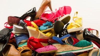 Untidy stack of shoes whose owner need to learn how to organize her home.
