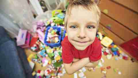 A boy with ADHD stands in the center of a very disorganized room