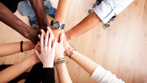 Hands doing a team-building cheer at a parent-teacher conference