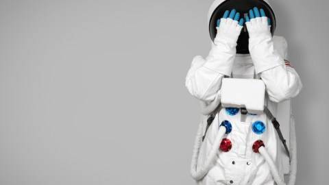 A woman with ADHD in an astronaut suit, covering her face. The condition can make you feel like you're from Mars.