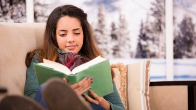 A woman with ADHD reads a book, oblivious to any other obligations.
