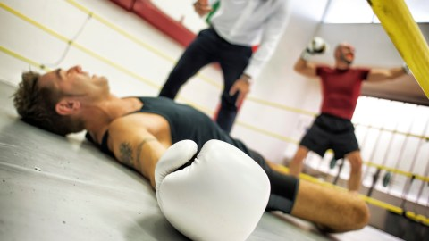 A boxer laying on the floor of the ring after losing a fight. He is weighed down by negative thoughts.