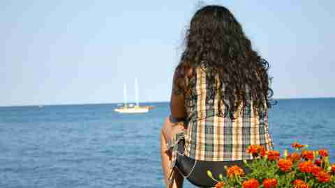 Girl looking out over bay and thinking positive affirmations