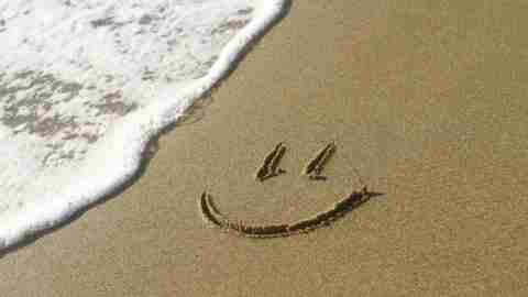 Happy face drawn in sand, representing positive affirmations