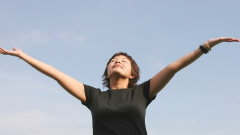 A woman with her arms outstretched, reciting positive affirmations