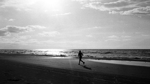 A black and white photo of a person jogging at the beach, a reminder that when you think you have ADHD it's a marathon, not a sprint.