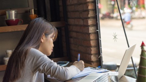 """A young woman works on paperwork at a cafe, and wonders, """"How does ADHD medication work?"""""""
