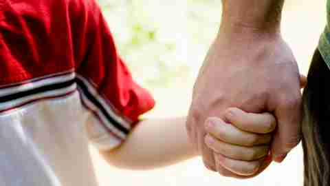 A father and son hold hands. Showing affection is one strategy for how to be a better dad.