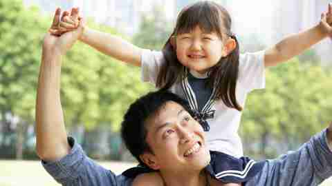 A father gives his daughter a ride on his shoulders in the park, one surefire way to be a better dad.