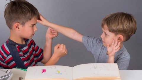 Two boys argue in front of a drawing pad. They could use YouTube videos for kids to improve their social skills.