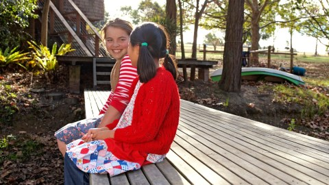 Two girls sit on a bench outdoors talking. They learned social skills through YouTube videos for kids.