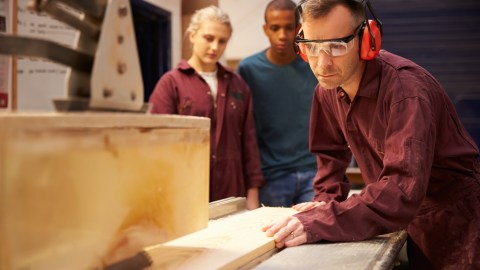 A shop teacher demonstrating woodworking to two students, since vocational training can help improve the education system