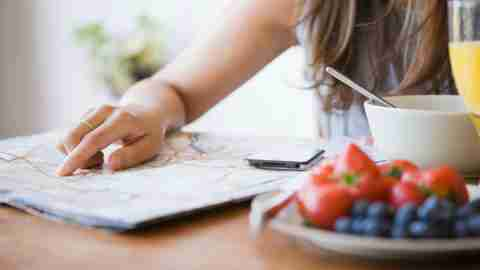 A woman looks at a map, and eats yogurt with berries, a quick recipe idea.
