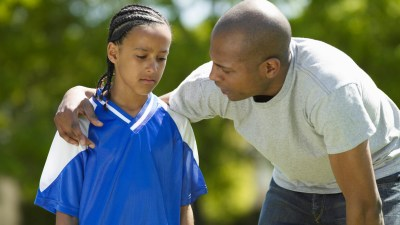 A young ADHD boy experiencing anxiety at an after-school soccer game and being comforted by his father