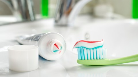 Toothbrush and toothpaste in the bathroom close up.