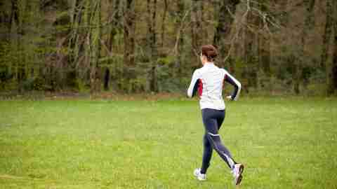 woman with SPD running in beautiful park with green grass