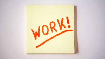 """Yellow sticky note on white wall with word """"Work!"""" on it, reminding people with ADHD to work on their careers"""