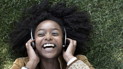 Overjoyed woman with ADHD laying on grass listening to music and laughing