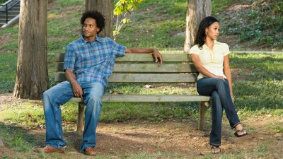 Man and woman with ADHD sitting on either side of a bench in a park