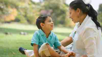 Mother talking to son with ADHD outside on grass