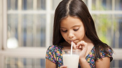 Girl with ADHD drinking milk with a straw in kitchen before bedtime to make her sleepy
