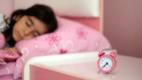 Girl with ADHD sleeping with alarm clock at bedside table
