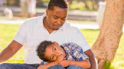 Boy with ADHD leaning on father in park outside