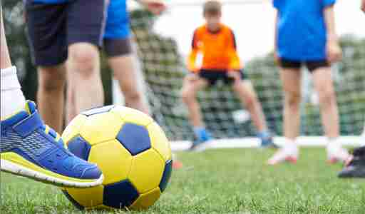 Close up of ADHD child's foot on soccer ball preparing to kick a goal