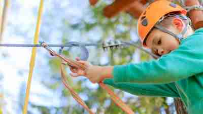 Boy with helmet and climbing gear getting ready to traverse obstacle course at ADHD Summer Camp