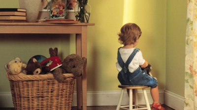 Child with ADHD sitting on bench in corner of room after being punished for impulsive behavior