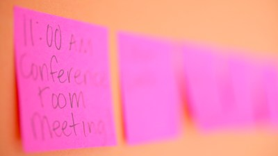 Row of pink sticky notes on orange wall reminding person with ADHD to exercise for brain power