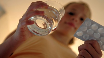 Girl with ADHD carrying glass of water and medication